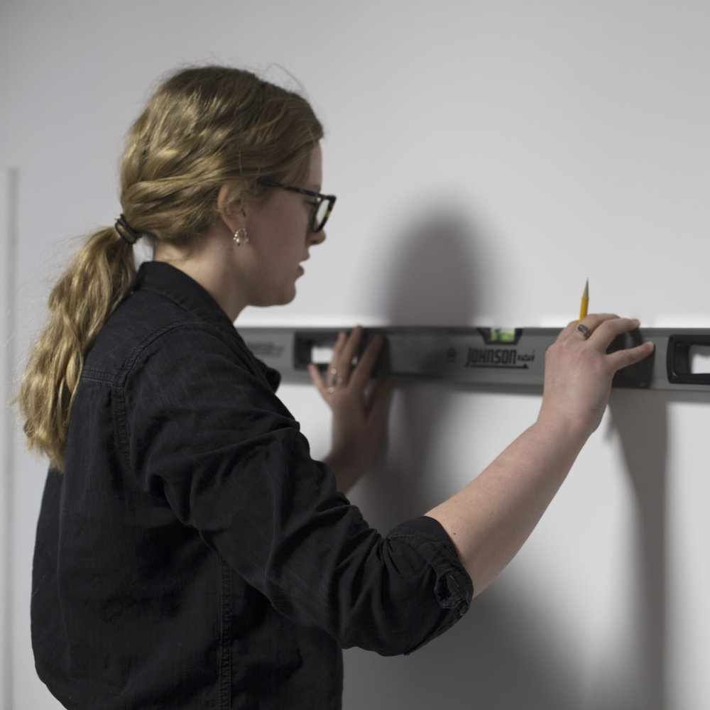 Person making a leveled line to install a sign