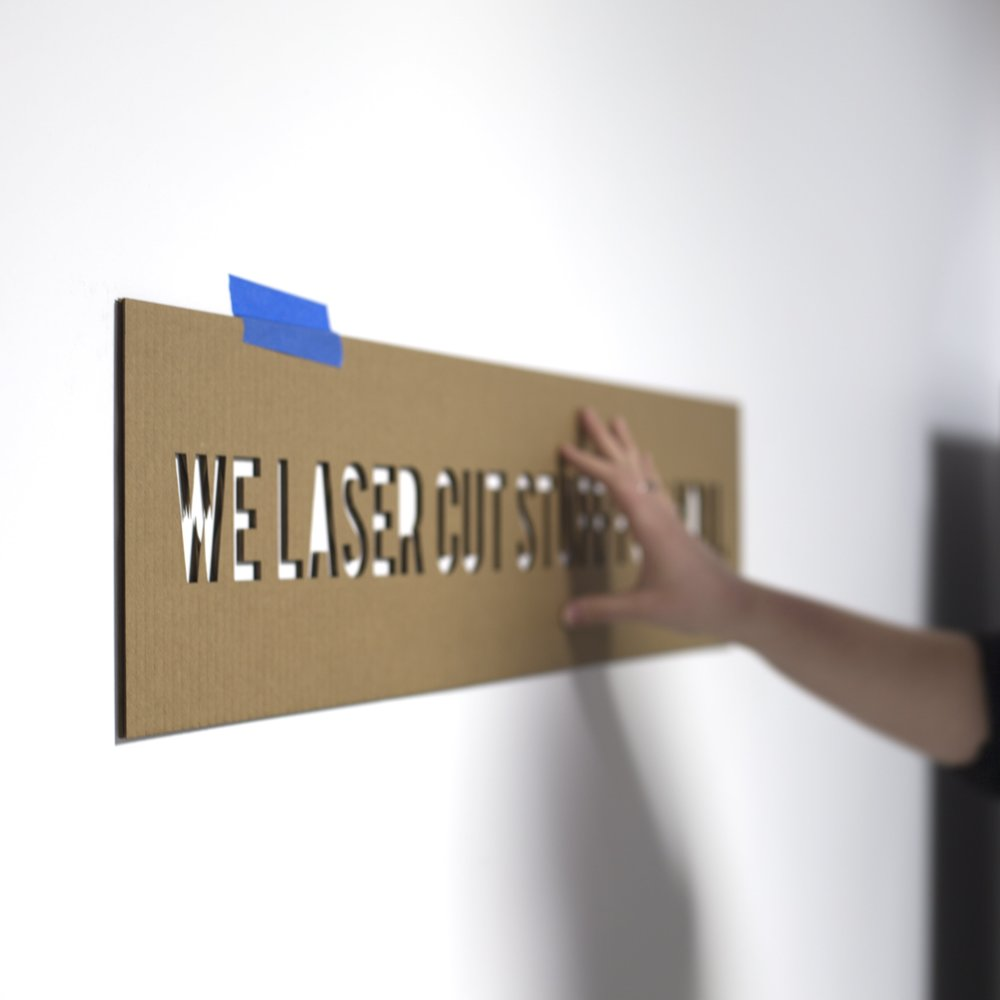 Person installing a laser cut sign with a cardboard template and tape