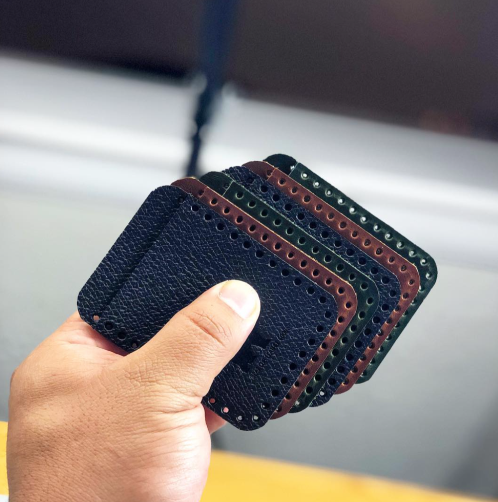 Leather punched phone pockets in hand created by Bear Cub Leather Goods in Houston, Texas