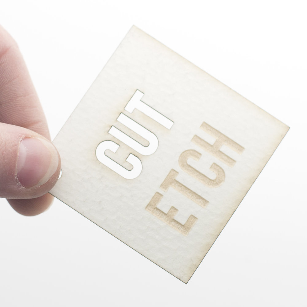 Cut and etch paper square sample cut by laser cut co being held in hand
