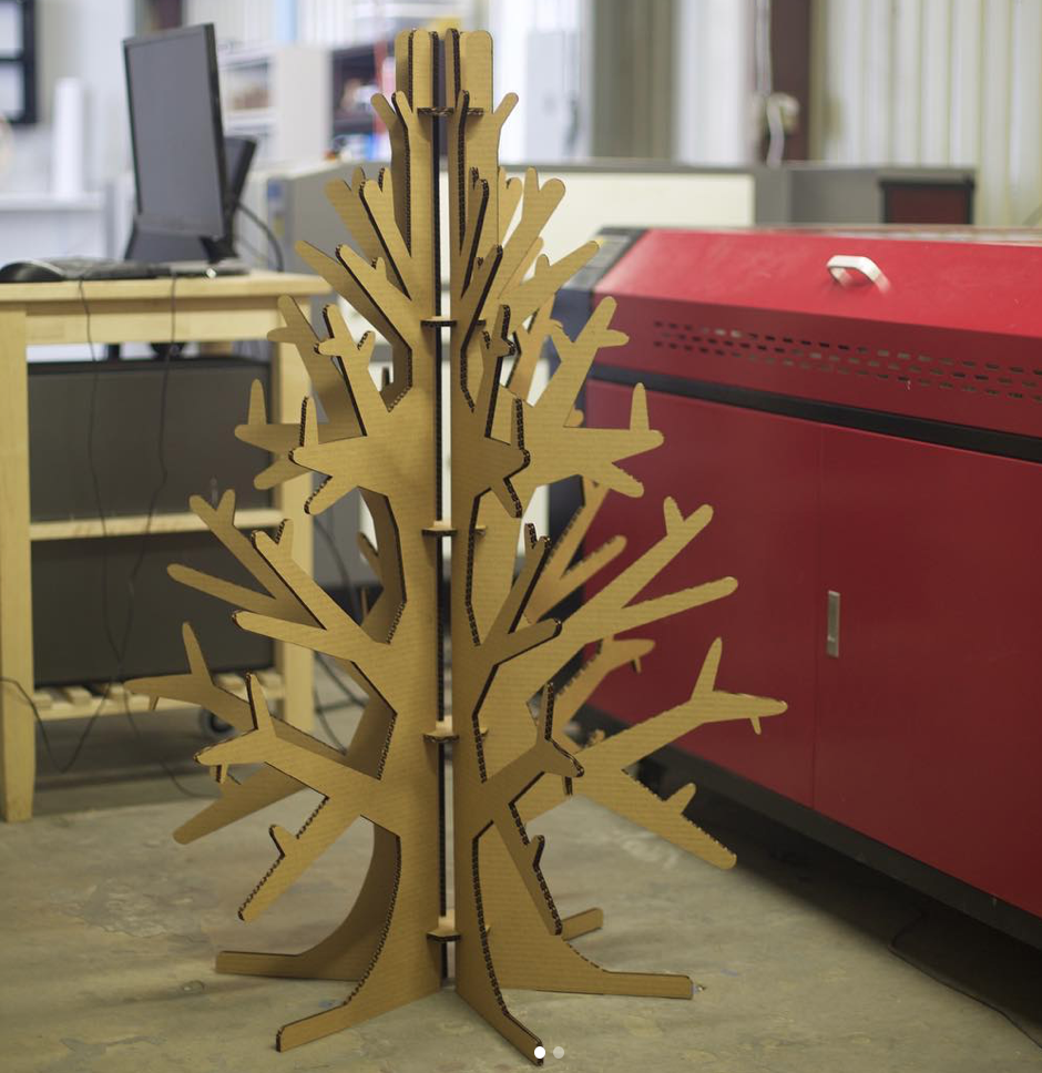 LaserCut Cardboard or Corrugated christmas tree for Holiday decor in front of laser cutter and computer station