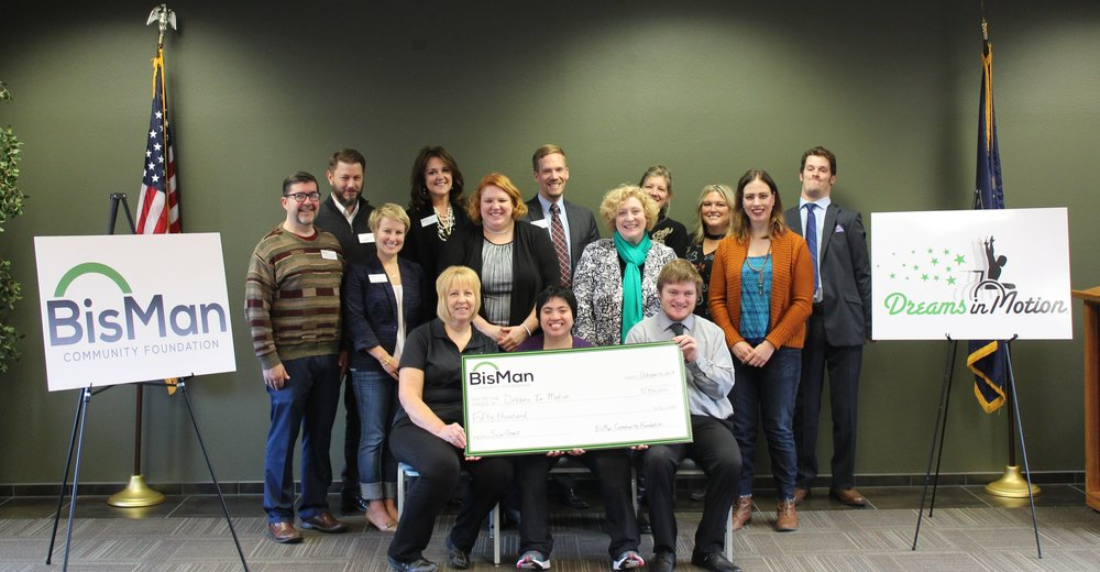 Members of the BisMan Community Foundation Advisory Committee and members of the Board of Directors of Dreams in Motion gathered for a photo after the award was made.