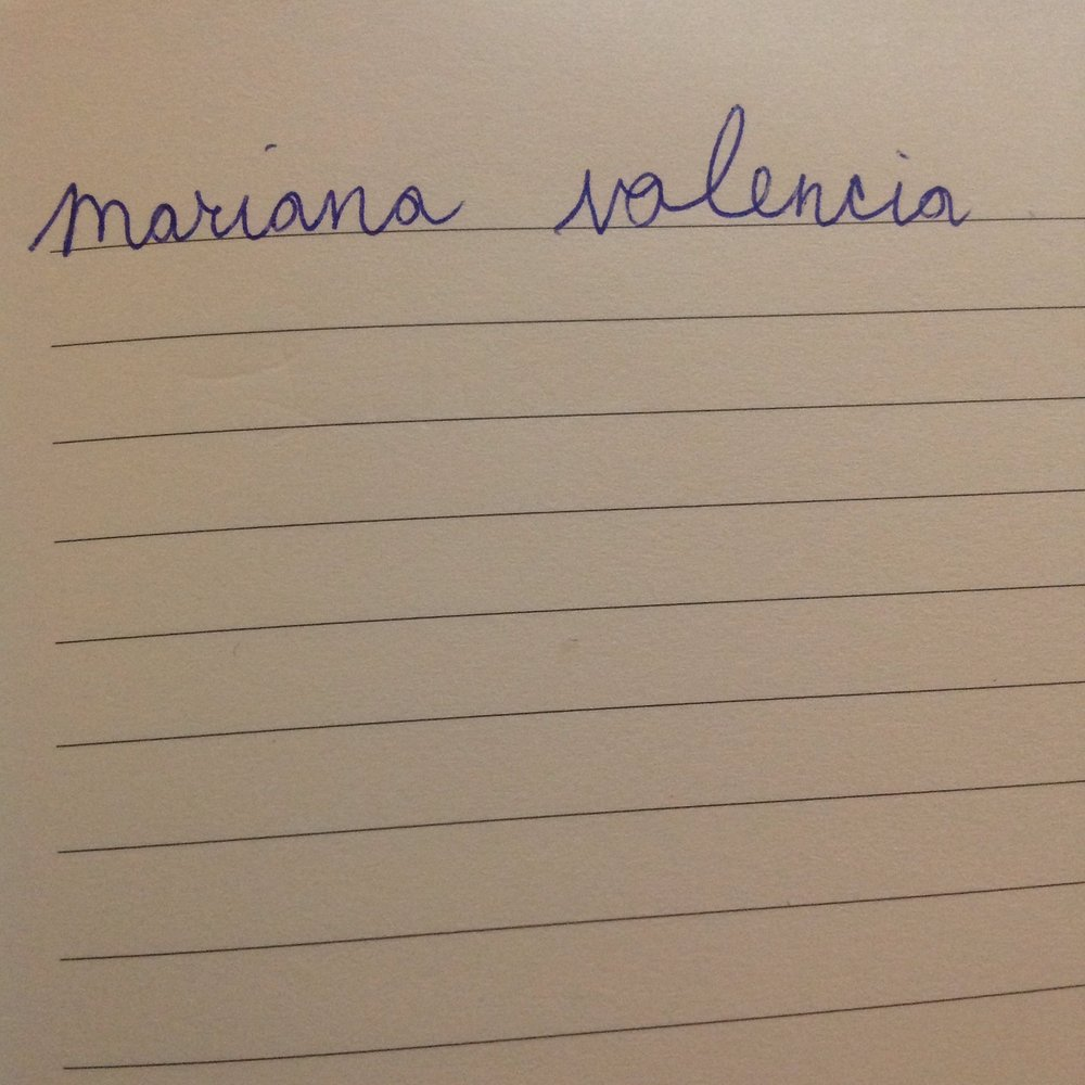 "visual description: a photo of lined paper with the words ""mariana valencia"" written on it"