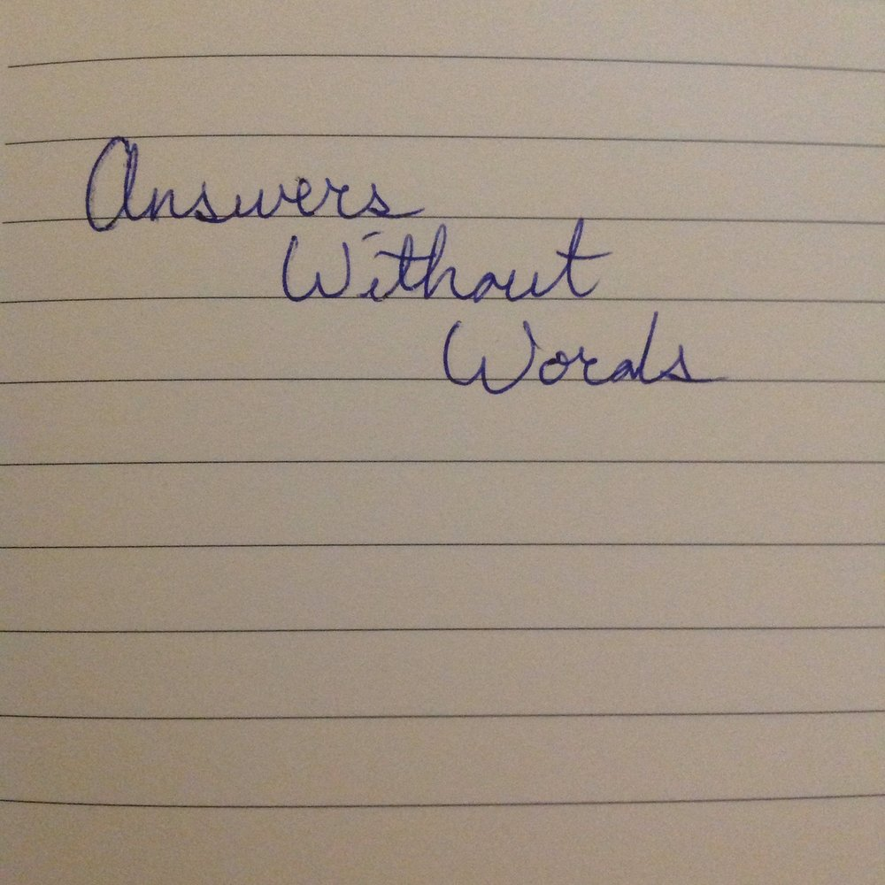 "visual description: an photo of lined paper with the phrase ""answers without words"" written in cursive"