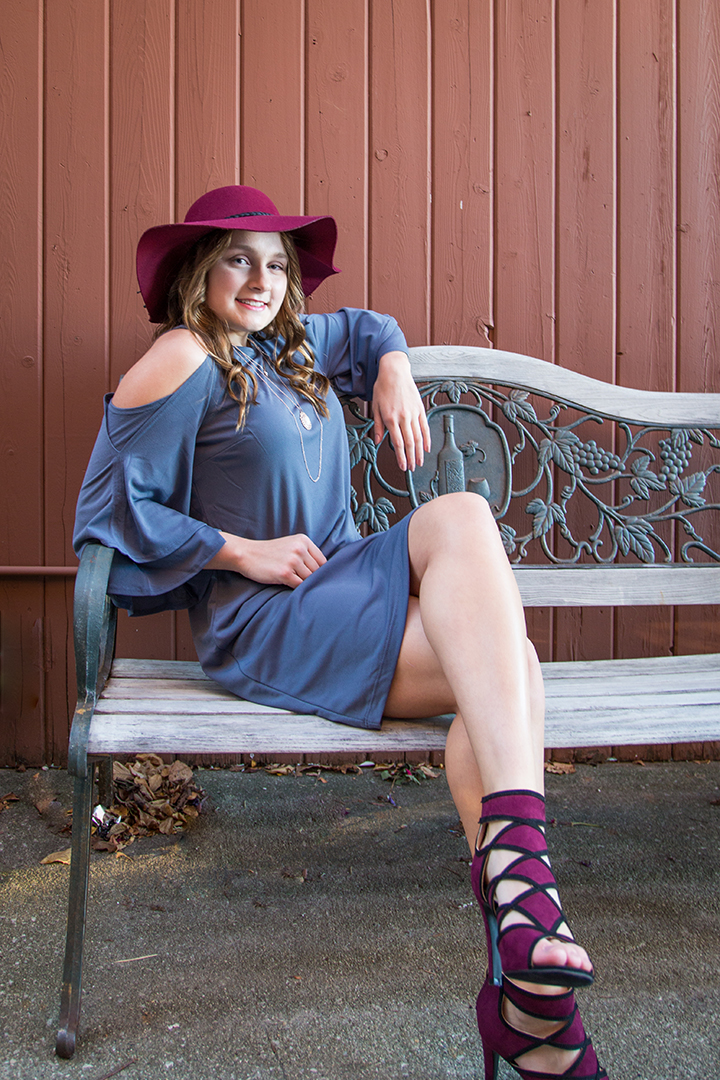 A high school senior photo of Veronica taken in downtown New Buffalo. Here she is sporting a lovely blue dress and red high heel shoes with complementary red summer hat while sitting on a wood bench.