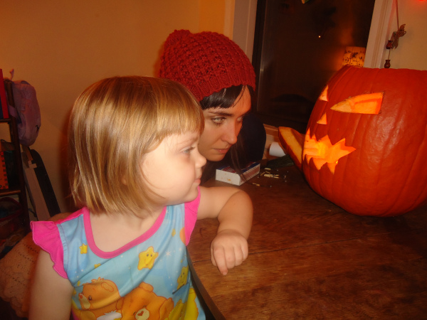 Brynn and Beatrix have a stare down with a pumpkin.