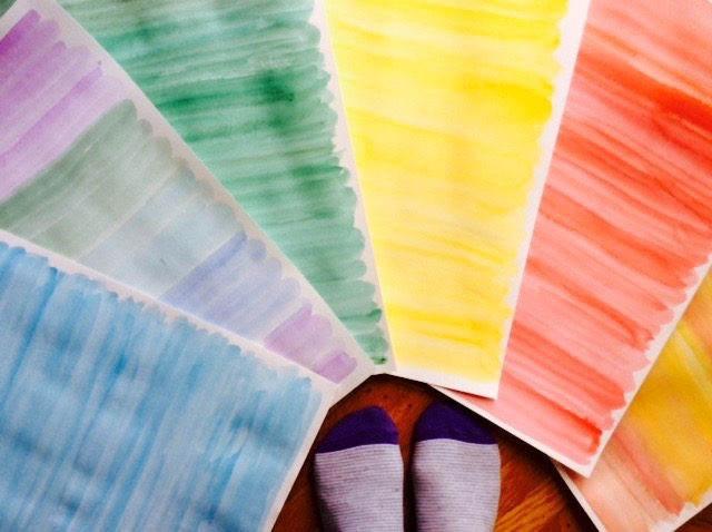 A rainbow of watercolor papers at my feet—the results of a productive play session.