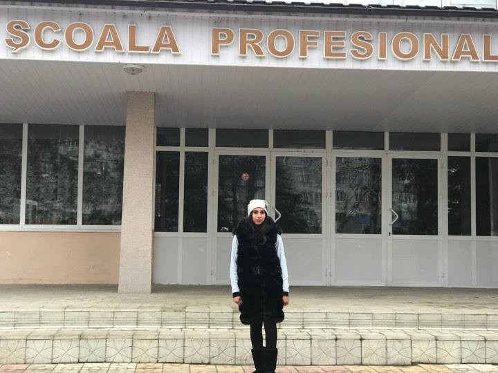 Stela poses outside her vocational school.