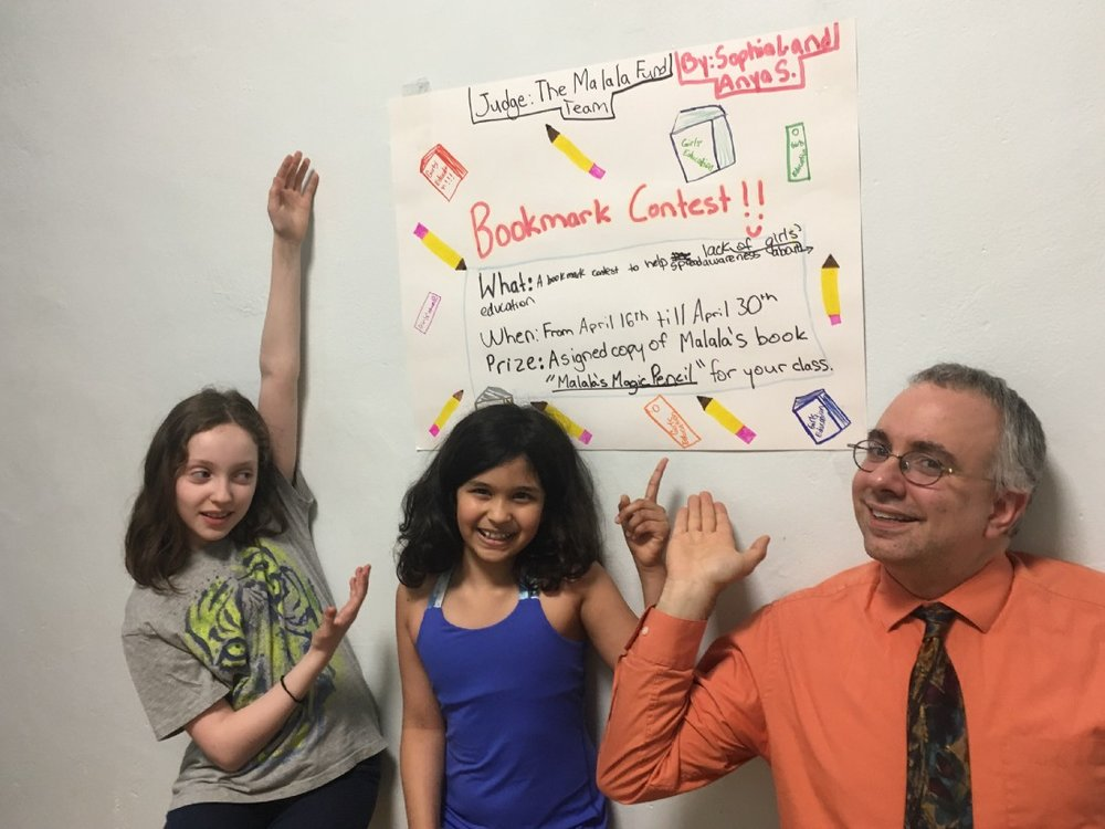 Anya (centre) poses with her friend Sophia (far left) and teacher Mr. Storti in front of a poster advertising the bookmark contest. (Courtesy of Anya Sen)