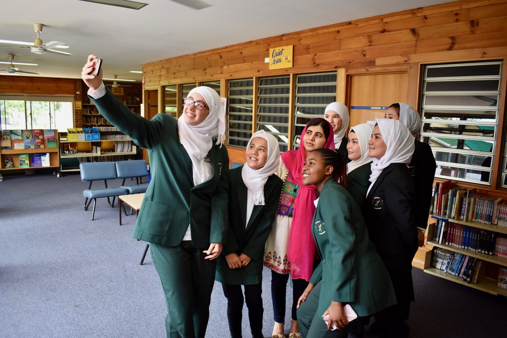 15-year-old Syrian refugee Rayaan takes a selfie with her friends and Malala Yousafzai at Holroyd High School. (Courtesy of Tess Thomas / Malala Fund)