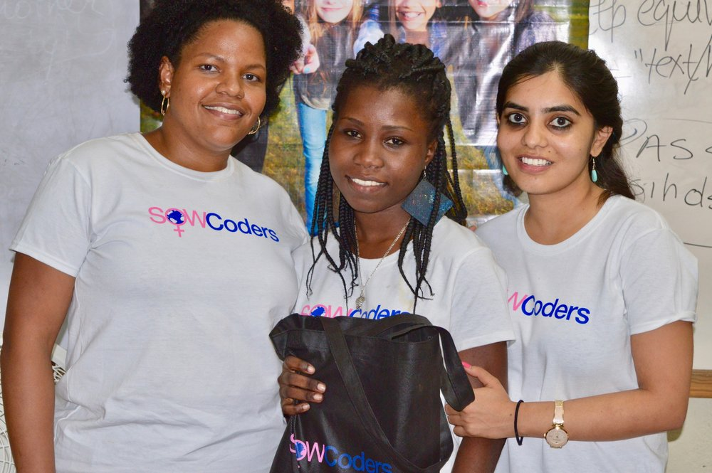 Belenda receives laptop for the best student award from SOWCoders co-founders. (Courtesy of SOWCoders)
