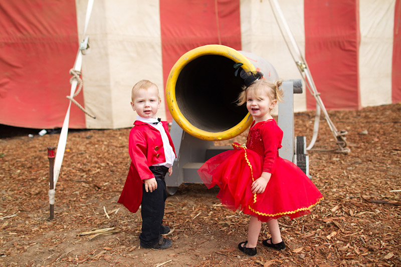 vintage circus wedding ring bearer dressed as ring master and flower girl standing next to canon