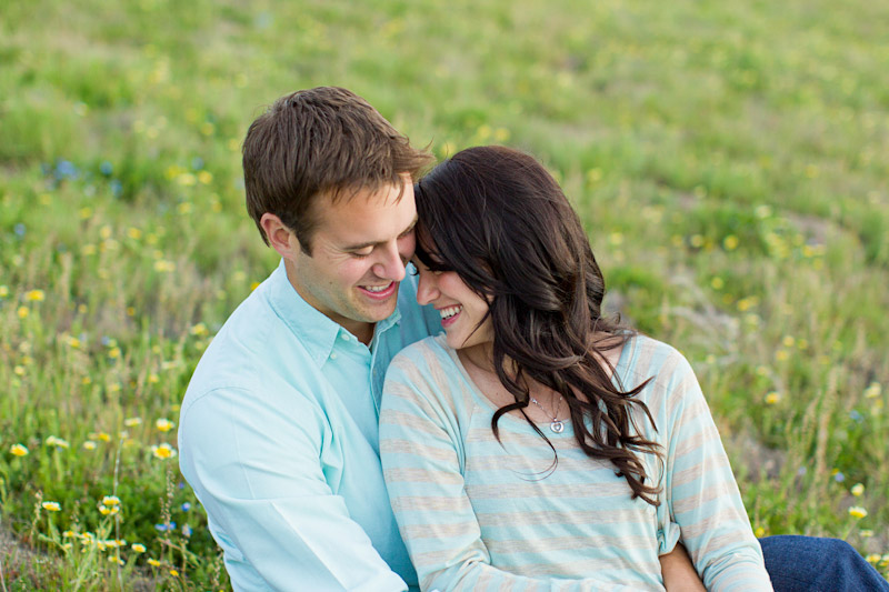 Santa Margarita wedding engagement picture of couple sitting in field laughing and hugging