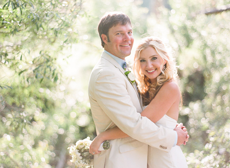Central Coast Avila Beach Golf Course wedding pictures of bride and groom hugging in front of trees