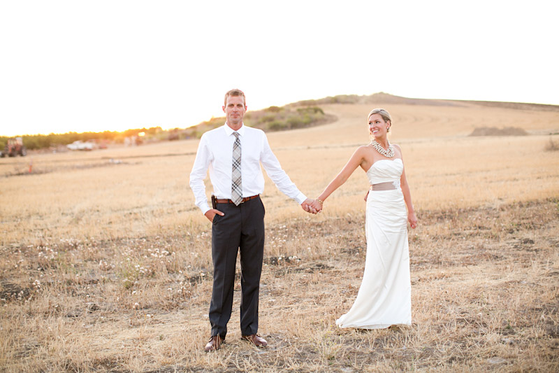 San Luis Obispo, Dana Powers Barn Wedding, bride and groom holding hands in an open field at sunset.