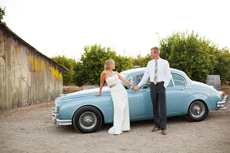 San Luis Obispo, Dana Powers Barn Wedding, bride and groom holding hands in front of a classic jaguar from Cars With Distinction.