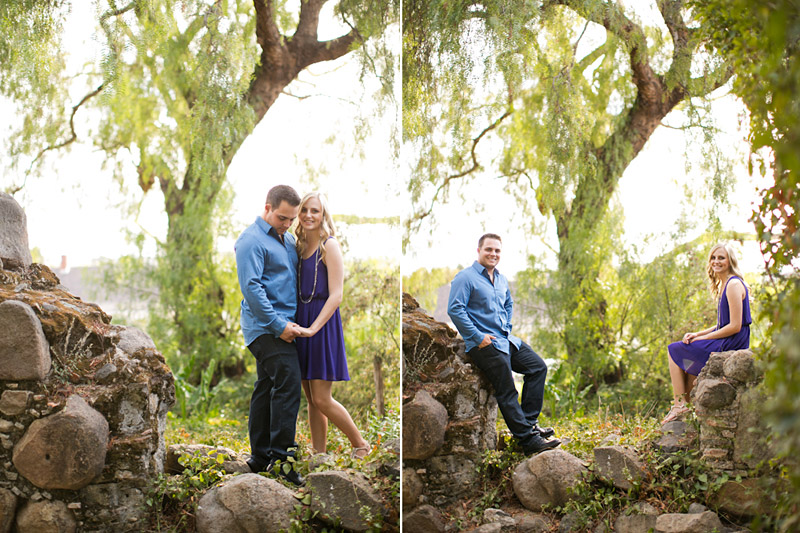 San Luis Obispo Engagement pictures of couple holding hands on a historic old mission wall surrounded by trees.