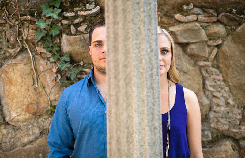 San Luis Obispo Engagement pictures of couple behind a light pole at historic old mission wall.