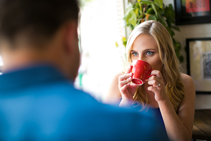 San Luis Obispo Engagement pictures of couple drinking coffee at cafe out of a red cup. (1 of 2)