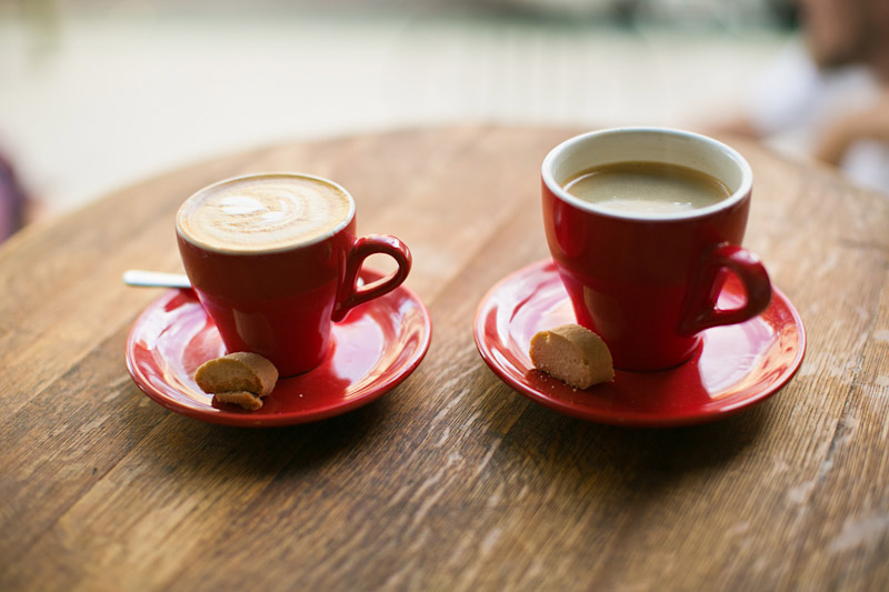 San Luis Obispo Engagement pictures of his and hers coffee in red cups.