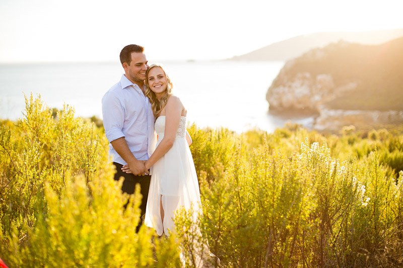 Avila Beach Engagement pictures of couple in glowing field on cliffs above the bay. (1 of 2)