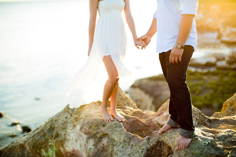 Avila Beach Engagement pictures of bride and groom holding hands from waist down on the cliffs overlooking Avila Bay.