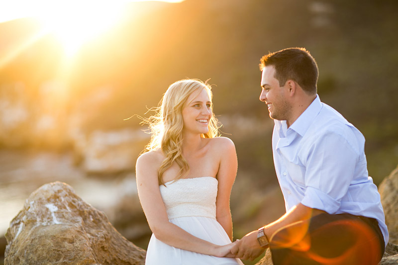 Avila Beach Engagement pictures of bride and groom holding sitting on rocks on the cliffs overlooking Avila Bay.