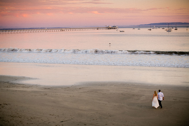 Avila Beach Engagement pictures of bride and groom walking on beach during pink sunset.