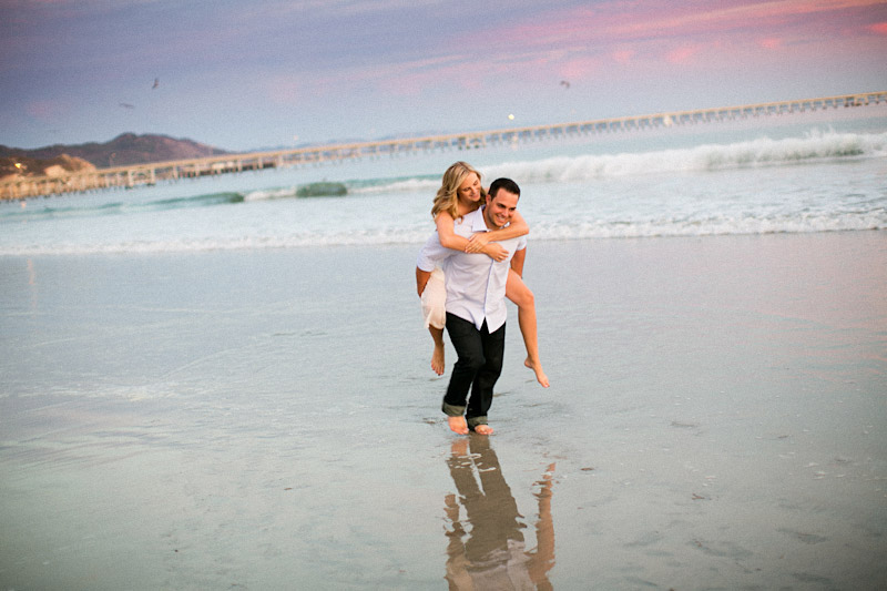 Avila Beach Engagement pictures of bride on groom's back running on beach during pink sunset.