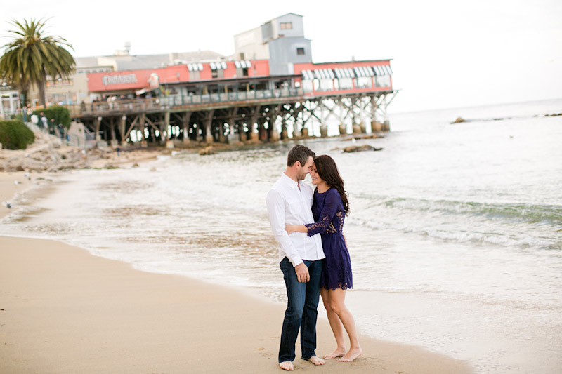 Monterey Engagement Photos of couple barefoot on beach.