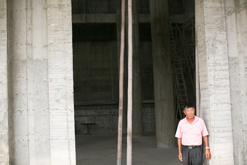 Taiwan wedding, temple that bride's father built by hand. Elderly man standing in large doorway.