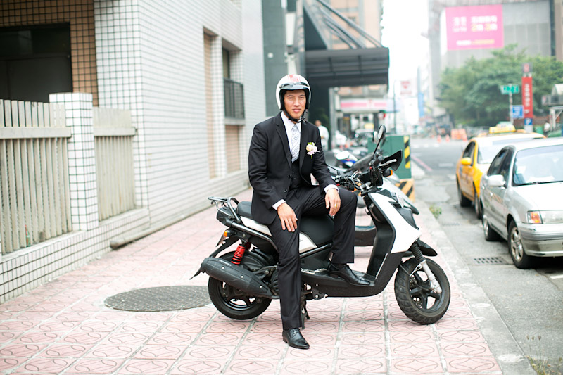 Taiwan wedding. Groom arriving on his scooter.