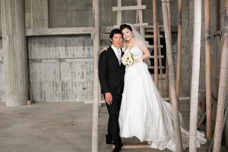 Taiwan wedding. Bride and groom on a ladder in unfinished temple.