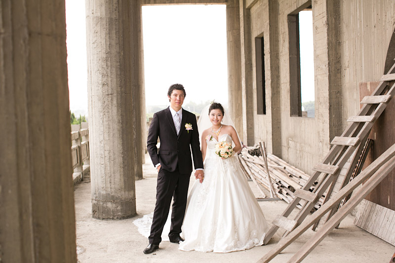 Taiwan wedding. Bride and groom holding hands around scaffolding at temple.