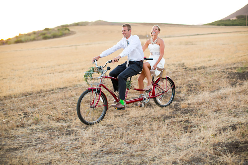 Dan Powers Barn, Bride and groom riding red vintage tandem bicycle through a field.