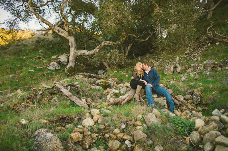 Morro Bay Engagement pictures of couple sitting on hill with trees & rocks by Cameron Ingalls. (1 of 2)
