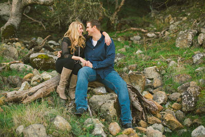 Morro Bay Engagement pictures of couple sitting on hill with trees & rocks by Cameron Ingalls. (2 of 2)