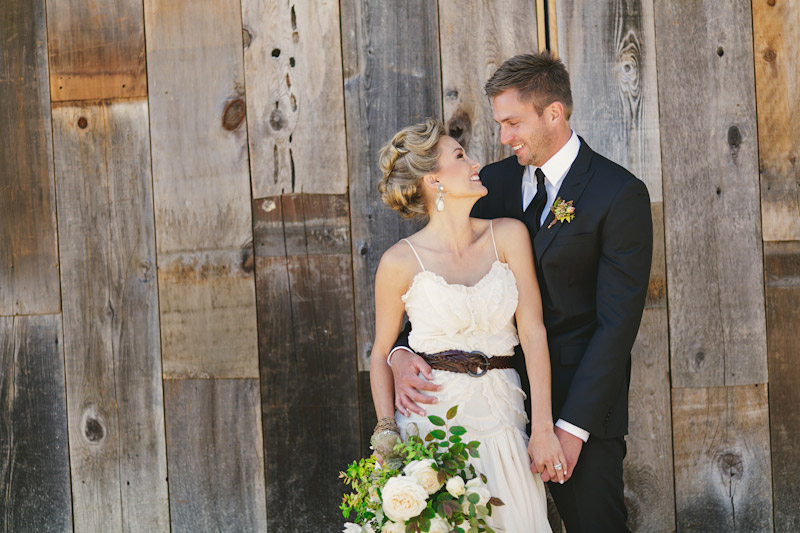 Central Coast rustic ranch wedding venue, Greengate ranch, couple holding each other and smiling front of barn.