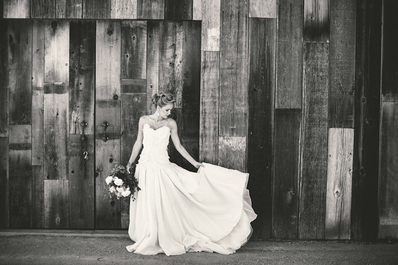 Central Coast rustic ranch wedding venue, Greengate ranch, bride in front of barn fluffing dress.