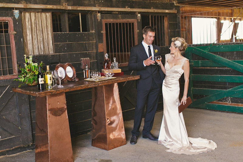 Central Coast rustic ranch wedding venue, Greengate ranch, couple at bar in horse barn drinking whiskey.