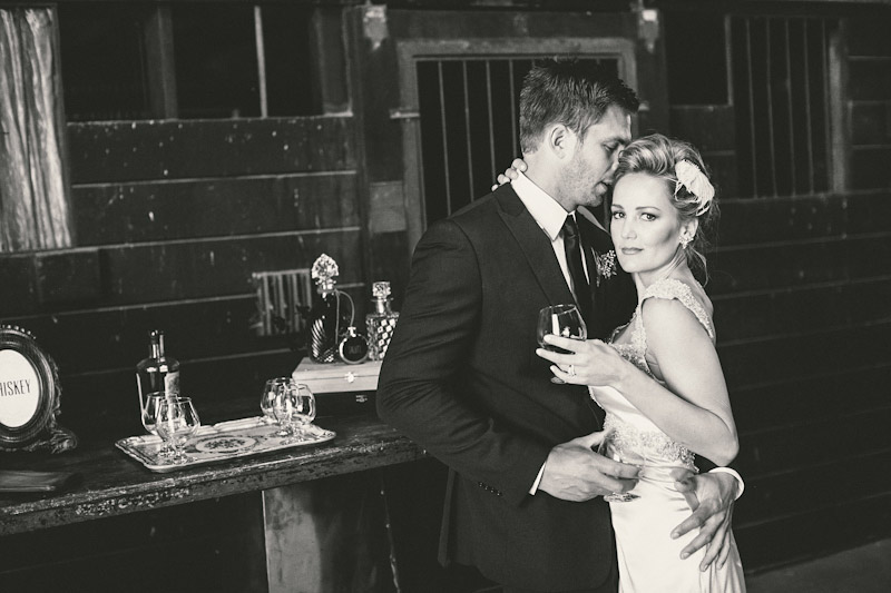 Central Coast rustic ranch wedding venue, Greengate ranch, bride and groom hugging at whiskey bar in horse barn.
