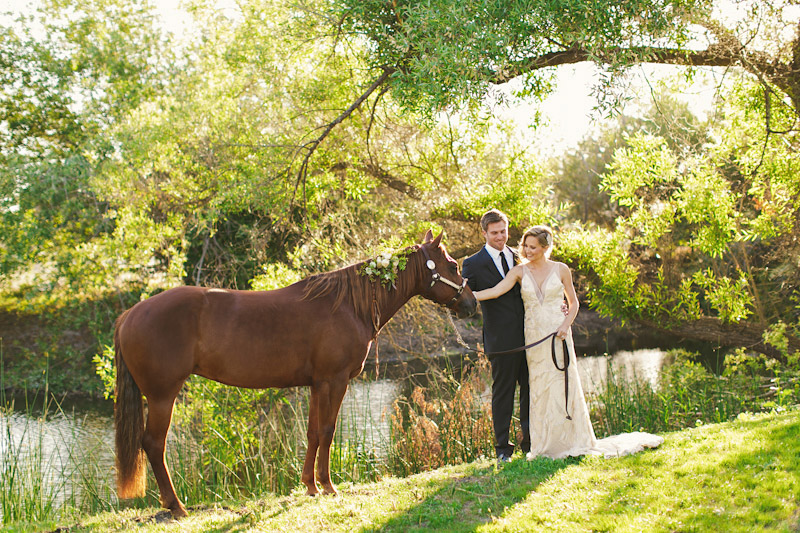 Central Coast rustic ranch wedding venue, Greengate ranch, bride& groom petting horse under tree near pond.