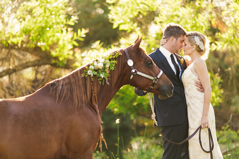 Central Coast rustic ranch wedding venue, Greengate ranch, bride& groom holding horse under tree near pond.