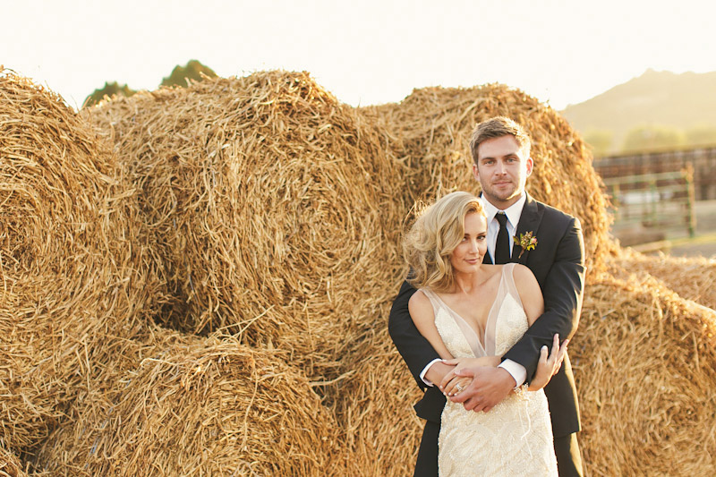 Central Coast rustic ranch wedding venue, Greengate ranch, bride and groom hugging in front of hay bales (1 of 2)
