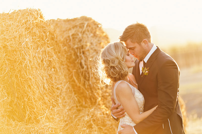 Central Coast rustic ranch wedding venue, Greengate ranch, table setting, bride and groom hugging in front of hay bales (2 of 2)