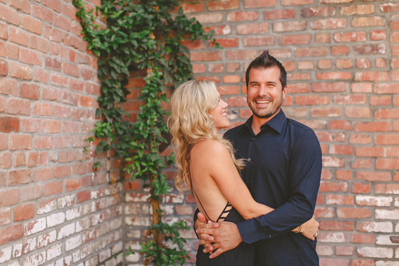 San Luis Obispo, Granada Hotel & Bistro, couple hugging in front of brick wall. (1 of 2)