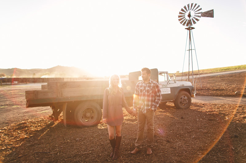 Greengate Ranch, San Luis Obispo, couple holding hands at sunset in front of vintage hay truck.