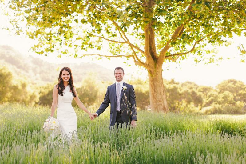 Carmel wedding, Carmel Valley Ranch, bride & groom holding hands in lavender field under tree on sunny afternoon.