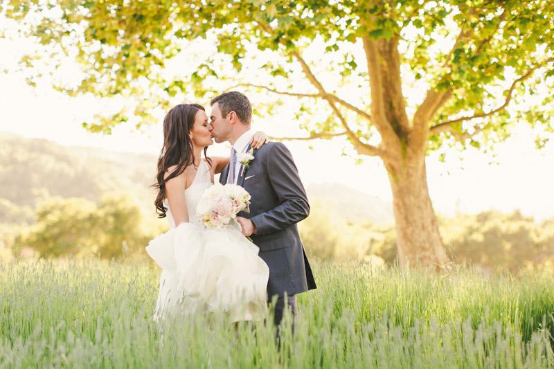 Carmel wedding, Carmel Valley Ranch, bride & groom kissing in lavender field under tree on sunny afternoon.