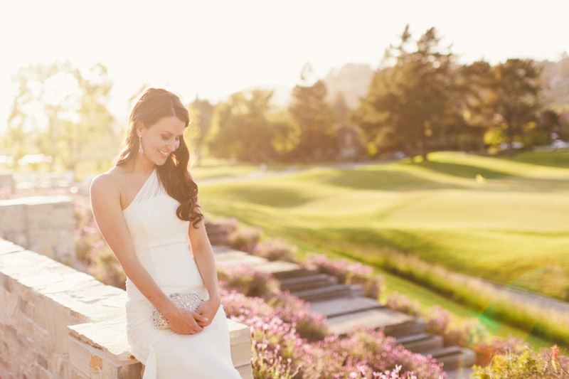 Carmel wedding, Carmel Valley Ranch, bride sitting and laughing in front of golf course.